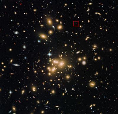 Figure 2 Imaginea de la telescopul spațial Hubble al NASA/ESA arată clusterul de galaxii Abell 1689 cu galaxia nou descoperită A1689-zD1 localizată în căsuța indicată, deși este atât puțin luminoasă încât abia se vede în această imagine.