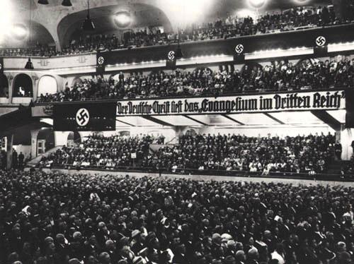 """Figura 2. Așa-numita """"Mișcare Creștină Germană"""" a dorit să obțină conformitatea organizațională și ideologică absolută între biserica protestantă și statul național-socialist. Pe banner scrie așa: Creștinul german citește """"Evanghelia în al treilea Reich""""."""