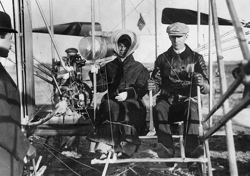 Frații Orville Wright, Katharine Wright și Wilbur Wright la Pau, Franța. Domnișoara Wright urmează să fie luată pentru prima ei plimbare într-un avion. 15 februarie 1909.
